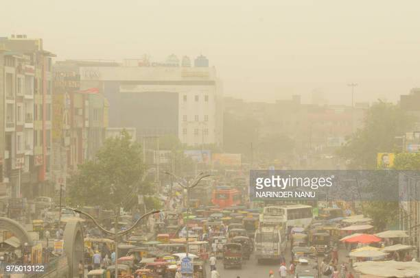 Commuters make their way as dust covers the sky at a bus stand in Amritsar on June 15 2018 Air pollution soared in New Delhi on June 14 to hazardous...
