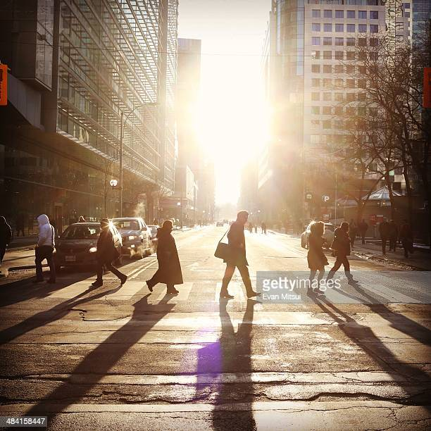 Commuters make their way home across Wellington Street in downtown Toronto as the March sun a rare sight this winter dips to the horizon
