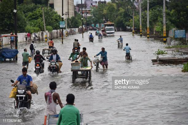 Commuters make their way on a waterlogged road following heavy rainfalls in Patna on September 30 2019 At least 100 people have died in northern...