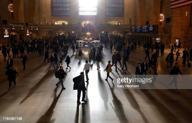 Commuters make their way through Grand Central Terminal as the sun rises through the east facade on October 28, 2019 in New York City.