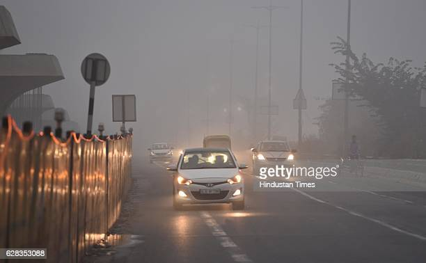 Commuters make their way through the thick fog and cold weather on December 7 2016 in New Delhi India Fog over parts of north India continued to...