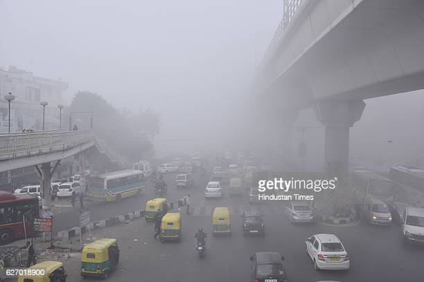 Commuters make way on cycles through morning fog at luxmi Nagar on December1 2016 in New Delhi India Traffic was moving slowly especially on the...