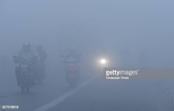 Commuters make way on cycles through morning fog on December1 2016 in New Delhi India Traffic was moving slowly especially on the DelhiNoida and...