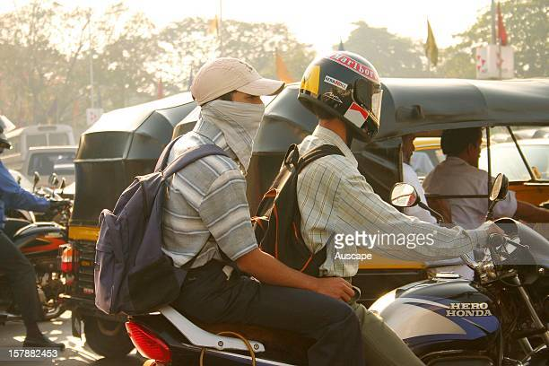 Commuters masked against air pollution negotiating city traffic Mumbai India