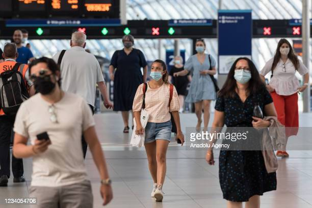Commuters, most of them continuing to wear face masks, walk through the concourse at London Waterloo railway station on the day of lifting of nearly...
