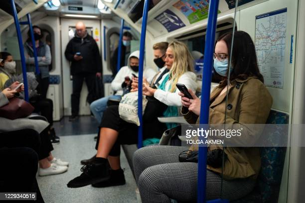 Commuters, most wearing masks because of the coronavirus pandemic, travel on a London Underground tube train in central London on October 29, 2020. -...