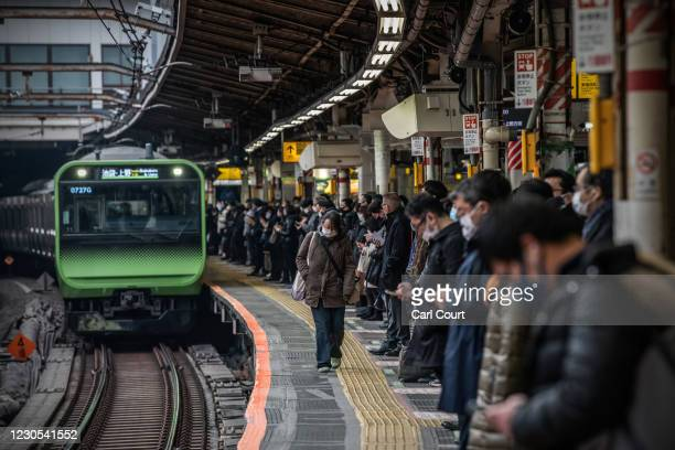 Commuters, mostly wearing face masks, wait for a Yamanote Line train as they travel to work during the first full week of Tokyos second state of...