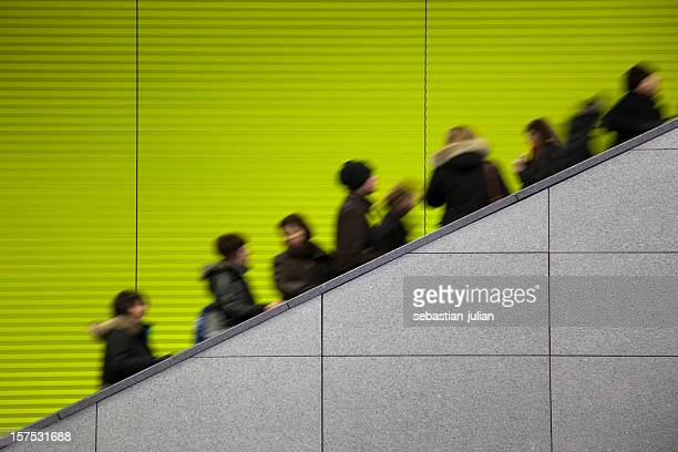 Commuters moving on escalator against a green background