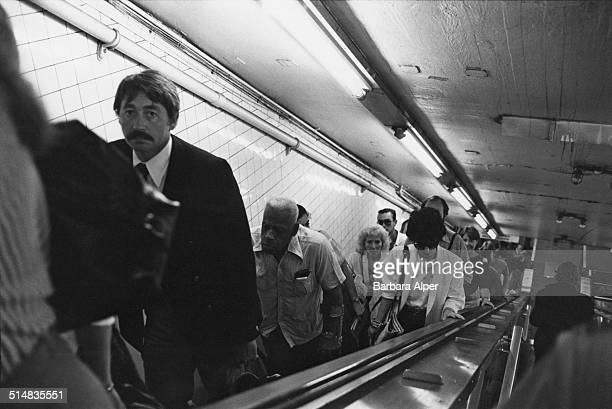 Commuters moving up a New York subway escalator New York City USA January 1982