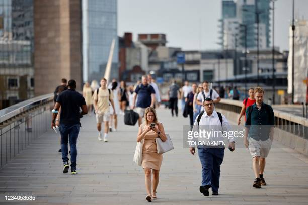 Commuters not wearing facemasks cross London Bridge in London on July 19, 2021. - Virtually all pandemic restrictions were lifted in England today...