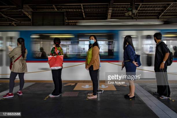 Commuters observe social distancing as they queue to get on trains on the first day of relaxed quarantine measures on June 1, 2020 in Quezon city,...