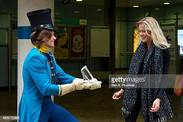 Commuters of London try their luck with Cinderella's glass slipper on a rainy Monday Morning at the Old Royal Naval College on the day of the film's...