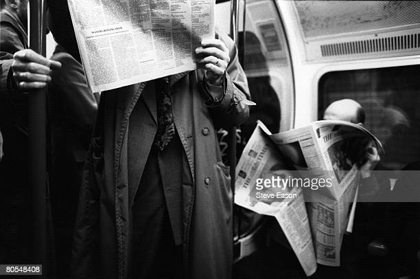 Commuters on a London Underground tube train reading their newspapers March 1993