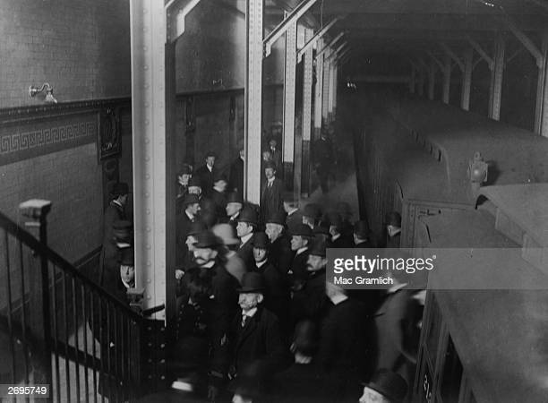 Commuters on a subway train exit onto a platform and move toward a stairwell New York City The subways cars are covered with soot