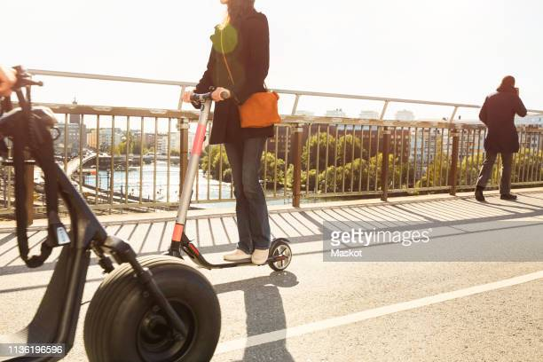 commuters on bridge against sky in city - electric scooter stock pictures, royalty-free photos & images