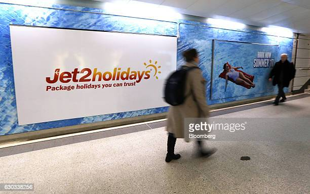 Commuters pass a poster advertising Jet2com holidays at Liverpool Street railway and underground station in London UK on Wednesday Dec 21 2016 The...