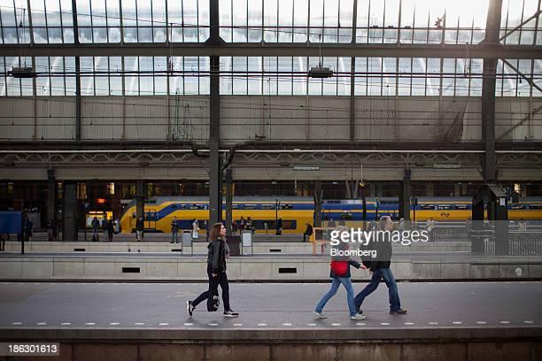 Commuters pass along a platform as a Koploper passenger train operated by Nederlandse Spoorwegen stands beyond at Amsterdam Centraal station in...