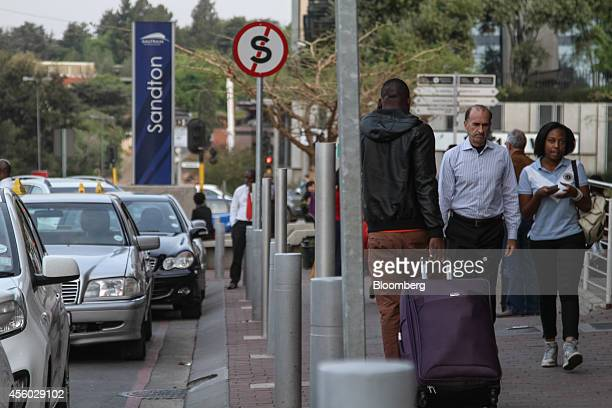 Commuters pass along a sidewalk outside the Gautrain station in Sandton South Africa on Tuesday Sept 23 2014 Sandton once a single 20story tower and...