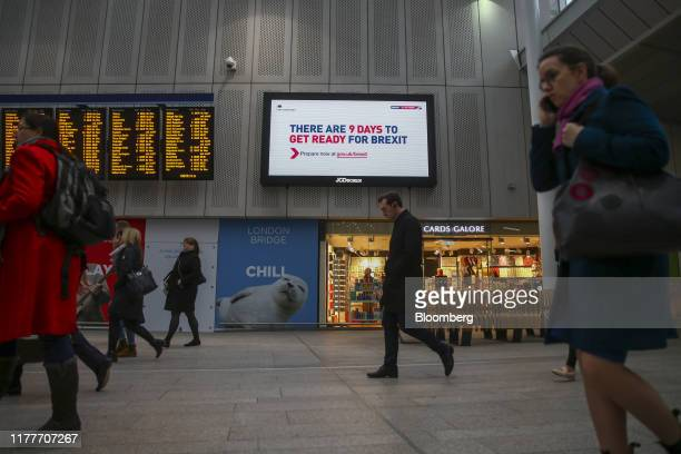 """Commuters pass an electronic billboard, operated by JCDecaux SA, featuring the the U.K. Government's """"Get ready for Brexit"""" advertising campaign at..."""