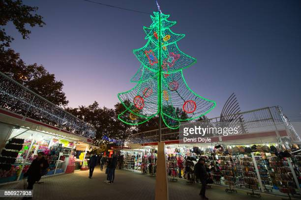 Commuters pass an outdoor market with an illuminated Christmas tree at Aluche train and metro station during the annual Christmas holiday season on...