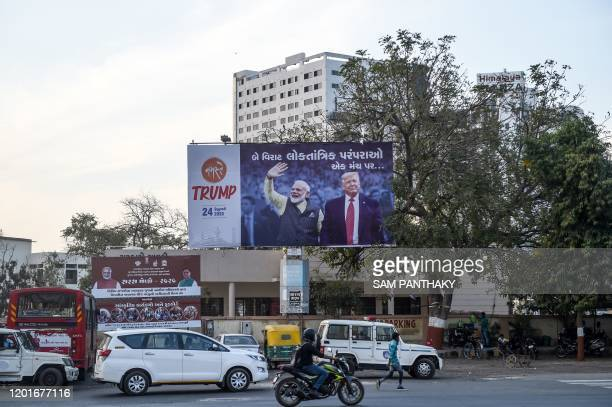 Commuters pass below a billboard depicting US President Donald Trump and India's Prime Minister Narendra Modi in Ahmedabad on February 18 2020 Donald...