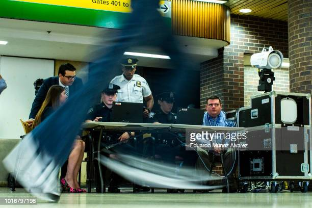 Commuters pass by as Port Authority police officers test new devices designed to detect explosives at the Port Authority Bus Terminal on August 14...