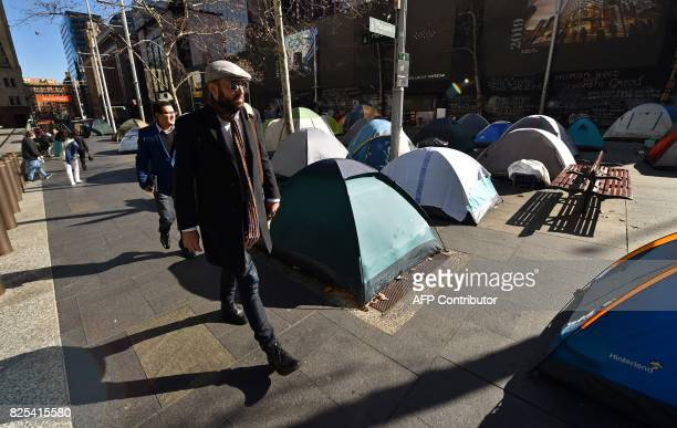 Commuters pass by tents set up in Martin Place which has become known as 'Tent City' as homeless people set up camp in the central business district...