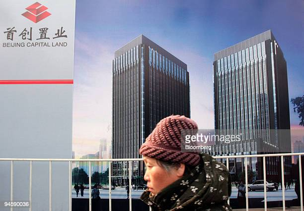 Commuters pass by the site of The Center, a Beijing CapitaLand Ltd. Project in Beijing, China, on Wednesday, March 14, 2007. Beijing CapitaLand Ltd....