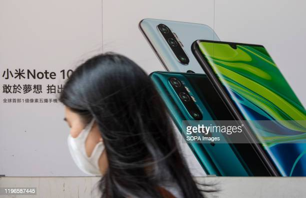 Commuters pass by Xiaomi Note 10 Pro smartphone advertisement at its flagship store in Hong Kong.