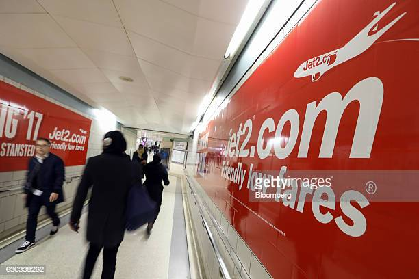 Commuters pass posters advertising Jet2com holidays at Liverpool Street railway and underground station in London UK on Wednesday Dec 21 2016 The...