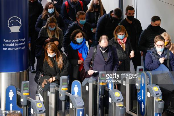 Commuters pass through a ticket barrier at London Waterloo railway station in London, U.K., on Thursday, May 6, 2021. The U.K.'s economic rebound...
