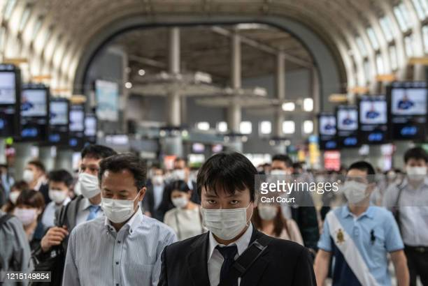 Commuters pass through Shinagawa train station the day after Japans state of emergency was fully lifted, on May 26, 2020 in Tokyo, Japan. As Covid-19...