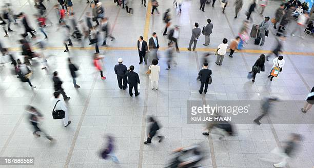 Commuters pass through the busy lobby of South Korea's largest combined railway and subway station in the crowded capital of Seoul on May 2 2013...
