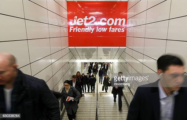 Commuters pass underneath a poster advertising Jet2com holidays at Liverpool Street railway and underground station in London UK on Wednesday Dec 21...