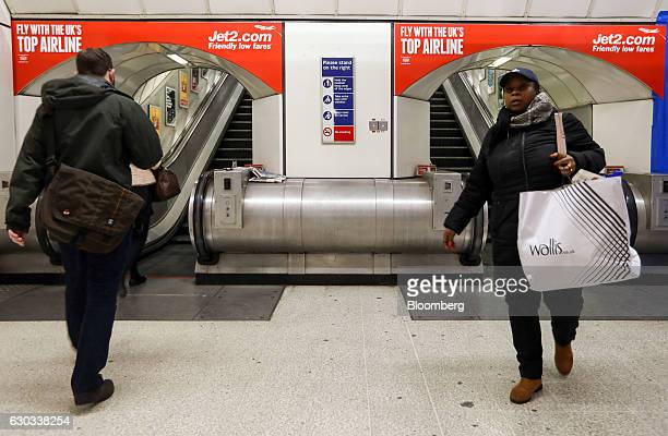 Commuters pass underneath posters advertising Jet2com holidays at Liverpool Street railway and underground station in London UK on Wednesday Dec 21...