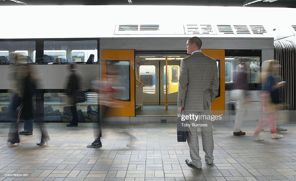 Commuters passing businessman on platform,  (blurred motion) : Stock Photo