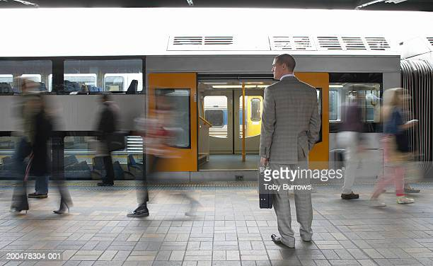 commuters passing businessman on platform,  (blurred motion) - railroad station stock pictures, royalty-free photos & images