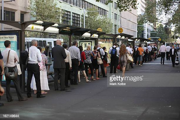 Commuters queue at a bus stop on York street in the CBD on February 19 2013 in Sydney Australia State Transit will be cutting buses on dead routes in...