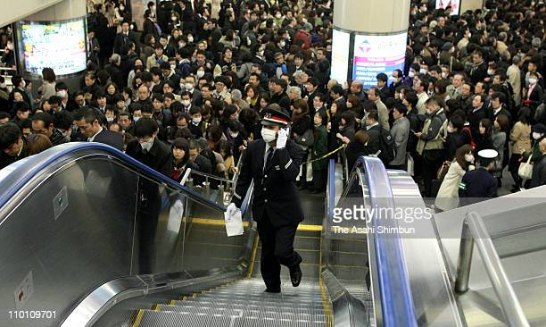 Commuters queue for trains as station officers try to organize the crowds during a rotated controlled power outage after several nuclear reactors...