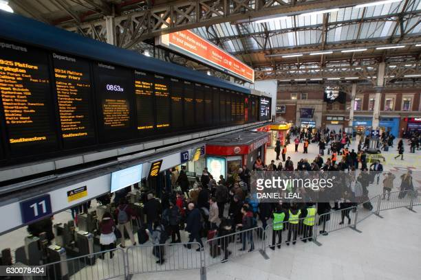 Commuters queue to take a train to Gatwick as strike action affects service at Victoria station in London on December 16 2016 Hundreds of thousands...
