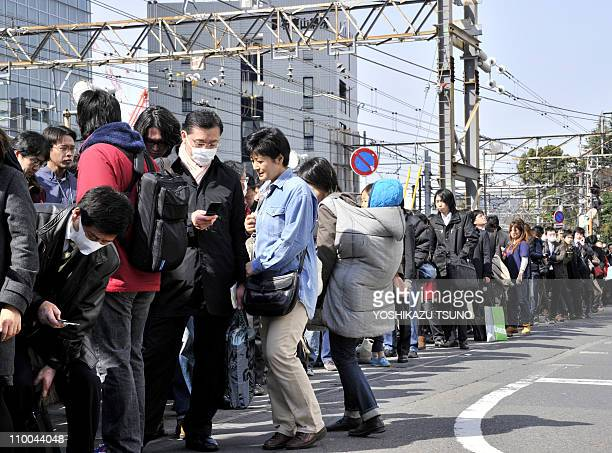 Commuters queue up waiting for train services to resume at Tokyo's Chofu station on March 14, 2011 as rail services around the capital were disrupted...