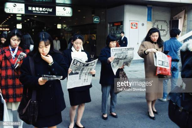 Commuters read extra edition of a newspaper reporting Emperor Hirohito died of cancer at JR Osaka Station on January 7 1989 in Osaka Japan
