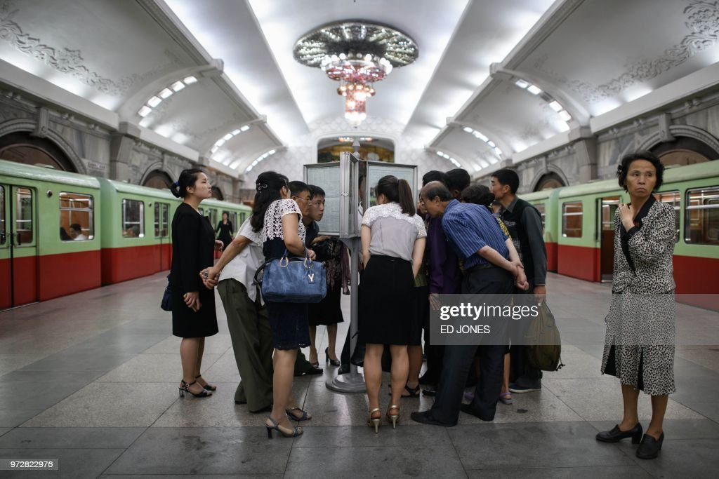 TOPSHOT - Commuters read the latest edition of the Rodong Sinmun newspaper showing images of North Korean leader Kim Jong Un meeting with US president Donald Trump during their summit in Singapore, at a news stand on a subway platform of the Pyongyang metro on June 13, 2018. - Donald Trump accepted an invitation from Kim Jong Un to visit North Korea during their historic summit, Pyongyang state media reported on June 13, as the US president said the world had jumped back from the brink of 'nuclear catastrophe'.