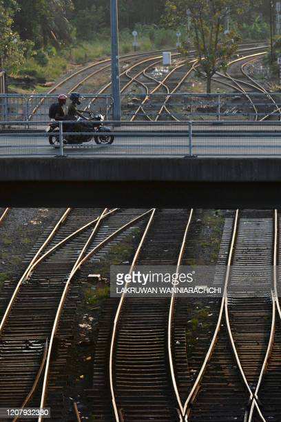 Commuters ride a motorbike through an empty bridge after the authorities announced a weekend curfew in the country as a preventive measure against...