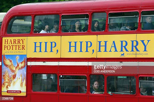 Commuters ride in a traditional English doubledecker bus adorned with an ad for the soontobereleased fifth Harry Potter book the 'Order of the...