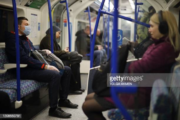 Commuters ride on a London Underground tube train in London on March 30 as life in Britain continues during the nationwide lockdown to combat the...