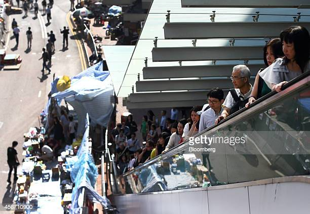 Commuters ride on an escalator on an elevated walkway leading to an entrance to the Central Government Offices in Hong Kong China on Monday Oct 6...