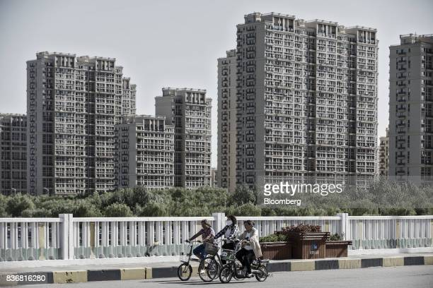 Commuters ride on bicycles past new residential buildings in Baotou, Inner Mongolia, China, on Friday, Aug. 11, 2017. China's economy showed further...