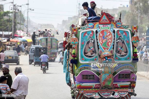 Commuters ride on top of a bus traveling through the Orangi town area of Karachi Pakistan on Wednesday Aug 23 2017 The murder of Orangi Pilot Project...