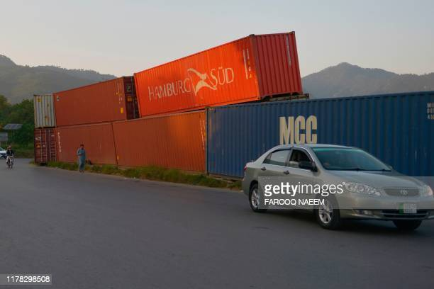Commuters ride past containers placed on roadside in Islamabad on October 26 ahead of opposition party Jamiat UlemaeIslam antigovernment protest ...